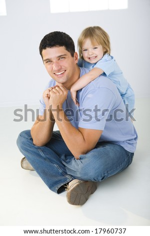 A man sitting on the floor with cross-legged and his daughter hugging him. They\'re smiling and looking at camera.