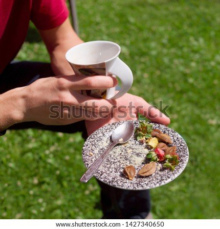 A man sitting outdoor with empty cup and empty plate