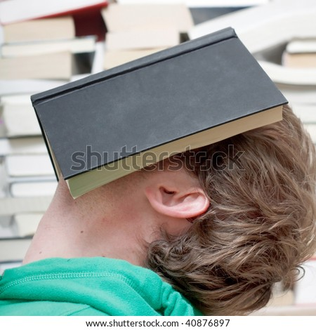 A man sleeping behind a book