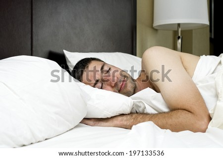 A man sleeping in a bed with white sheets.