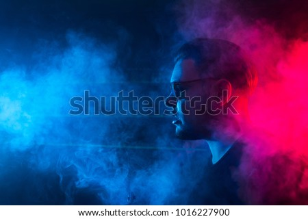 A man smokes a cigarette and lets out smoke in a nightclub. The neon light shines here. The guy in the sunglasses. #1016227900