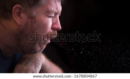 Photo of  A man sneezes and releases droplets in the air
