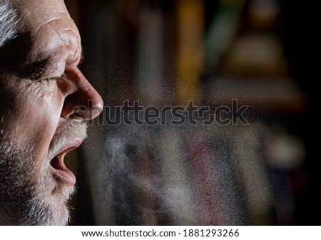 A man sprays aerosols into the air while speaking. Foto stock ©