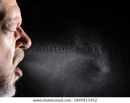 A man sprays aerosols into the air while speaking. The background is black. Foto stock ©