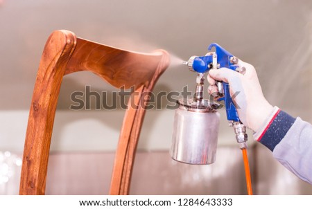 A man sprays with paint paints furniture wooden chair in the furniture industry. Closeup of spray bottle in hand. #1284643333