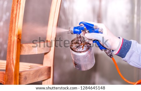 A man sprays with paint paints furniture wooden chair in the furniture industry. Closeup of spray bottle in hand. #1284645148