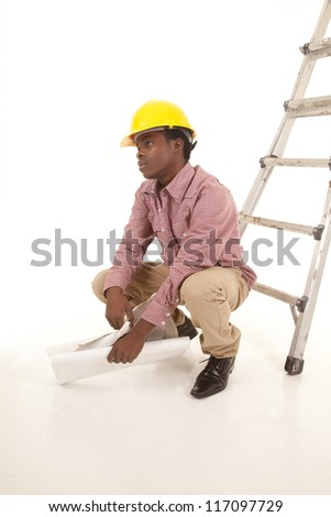 A man squatting down taking a break from his frustrations.
