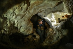A man squeezes into a narrow crevice and looks sideways at the wall of the karst cave inside the Mangup plateau in the Crimea. A man with backpack is dressed in a brown windbreaker. Head torch on.