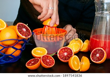 A man squeezes orange juice into a juicer from Tunisian oranges. A basket of oranges, halved oranges, orange peels and a decanter of orange juice next to the juicer.