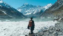 A man stand alone to Mt. cook peak, Tasman lake, in Newzealand