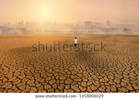 a man standing at empty land of dry cracked earth and looking to the big city with air polluted environment metaphor Climate change, Water crisis, Environment pollution of activity from urban concept. #1458006029