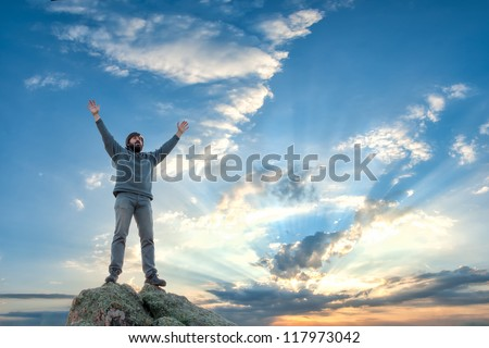 A man standing at mountain top with open arms, beautiful sunrise on background