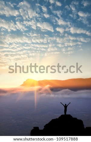 A man standing at mountain top with open arms set against a beautiful sunrise