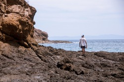 A man standing at the rocks looking at the horizon at the sea surrounded by rocks. Blue ocean. Blue mountains far away. Socialdistancing.