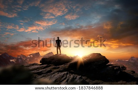 A man standing at the top of a mountain as the sun begins to set. Goals, hopes and aspirations concept. Photo compostion.