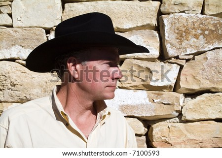 A man standing by a wall constructed of carefully placed cut stones and rock.