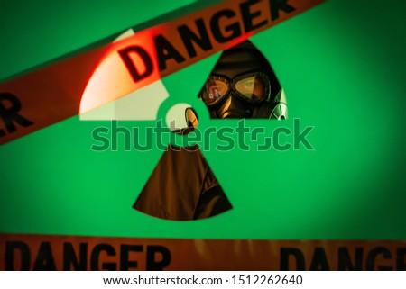 A man standing in a dark hoodie with a hood on his head with a gas mask on his face standing near the wall behind a fuzzy background with radiation tapes of danger