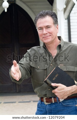 A man standing in front of a church holding a bible with his hand extended as if greeting someone.