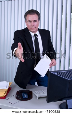 A man standing in front of a desk with his hand extended as if to greet someone.