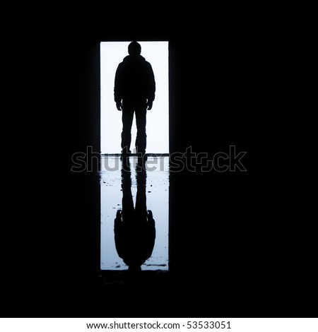 A man standing in front of a door with his image reflected on water - stock photo