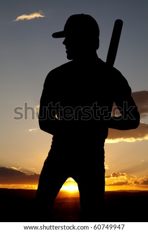 A man standing in the sunset holding his bat.