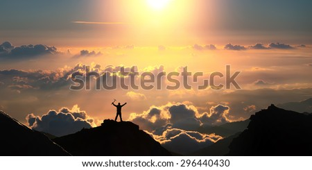 A man standing on the top of the mountain above the clouds with ice axe in his hands.