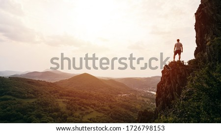 A man standing on top of a mountain as the sun sets. Goals and achievements concept photo composite. Concept vision, Hiker looking mountain and enjoying sunrise