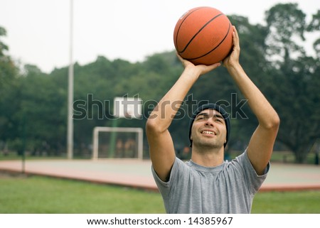 A man, standing tall, preparing to shoot a basketball while smiling, in a park - horizontally framed
