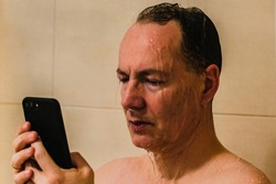 A man standing under a shower using a mobile phone in his hand  Showing always reachable, always working, always online