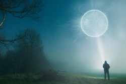 A man standing with a torch looking up at a glowing science fiction portal. On a foggy, winters night in the countryside.