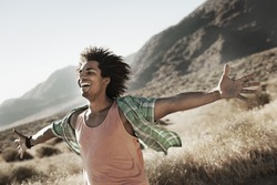 A man standing with arms outstretched in a gesture of freedom and excitement, leaning into the breeze