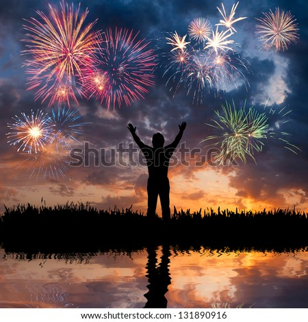 A man standing with open arms looks beautiful holiday fireworks feeling of freedom