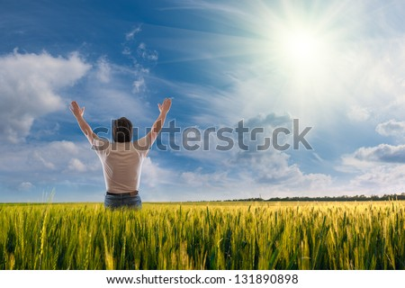 A man standing with open arms, sun in the sky, feeling of freedom