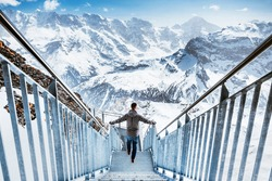A man stands at the beginning of a thrill walk on the top of Birg , in the background are the Swiss Alps.