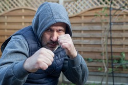 A man stands in the garden in a boxing stance.