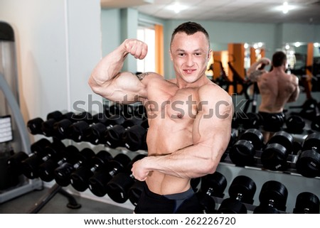 A man stands in the gym, flex arm, showing big muscles, pumped perfect body. Preparation for training, self-discipline. Naked torso. Be a good example for young people and society. row black dumbbell
