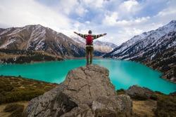 a man stands on a mountain, a mountain lake.Big Almaty Lake, Kazakhstan, Almaty