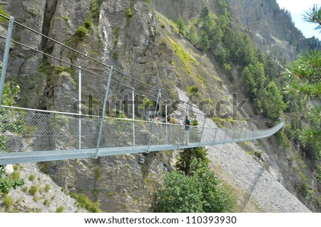 A man stands on a very long steel suspension bridge for pedestrians over a deep chasm