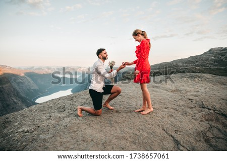 A man stands on his knee near the cliff and makes a creative proposal to a woman traveling in trolltunga, Norway. Emotional couple in love, engagement, rocks, nature, fjords. She said yes on the top. Stock photo ©