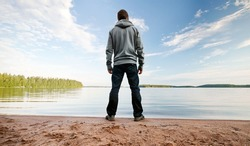 A man stands on the sand lake coast starring at the horizon