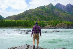 a man stands on the shore of a mountain river