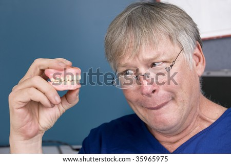 A man stares at his dentures before putting them back in his mouth.