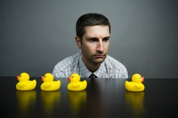 A man staring at four yellow rubber ducks placed on a table.