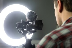 A man streaming through the Internet, video recording with a mirrorless camera and ring light.