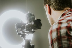 A man streaming, video recording using a mirrorless camera and ring light.