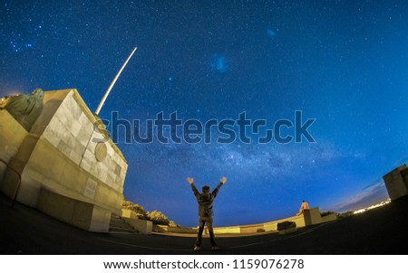 A man stretches his arms and reach for the sky. The night sky is beautiful and full of stars. One can see milky way galaxy. This photo is suitable for inspirational purpose to motivate people in life.