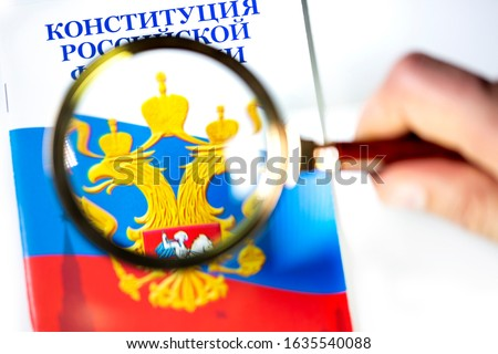A man studies The Constitution of the Russian Federation under a magnifying glass on white background. The Russian inscription on the photo reads 'The Constitution of the Russian Federation' Foto stock ©