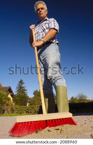A man sweeps with a new red broom.