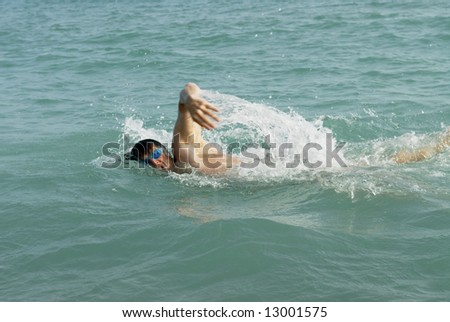 A man swimming the front crawl in the sea.
