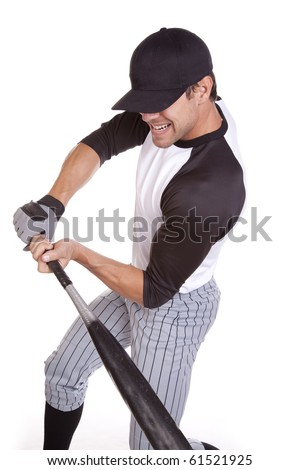 A man swinging his bat hard at the ball that is coming.